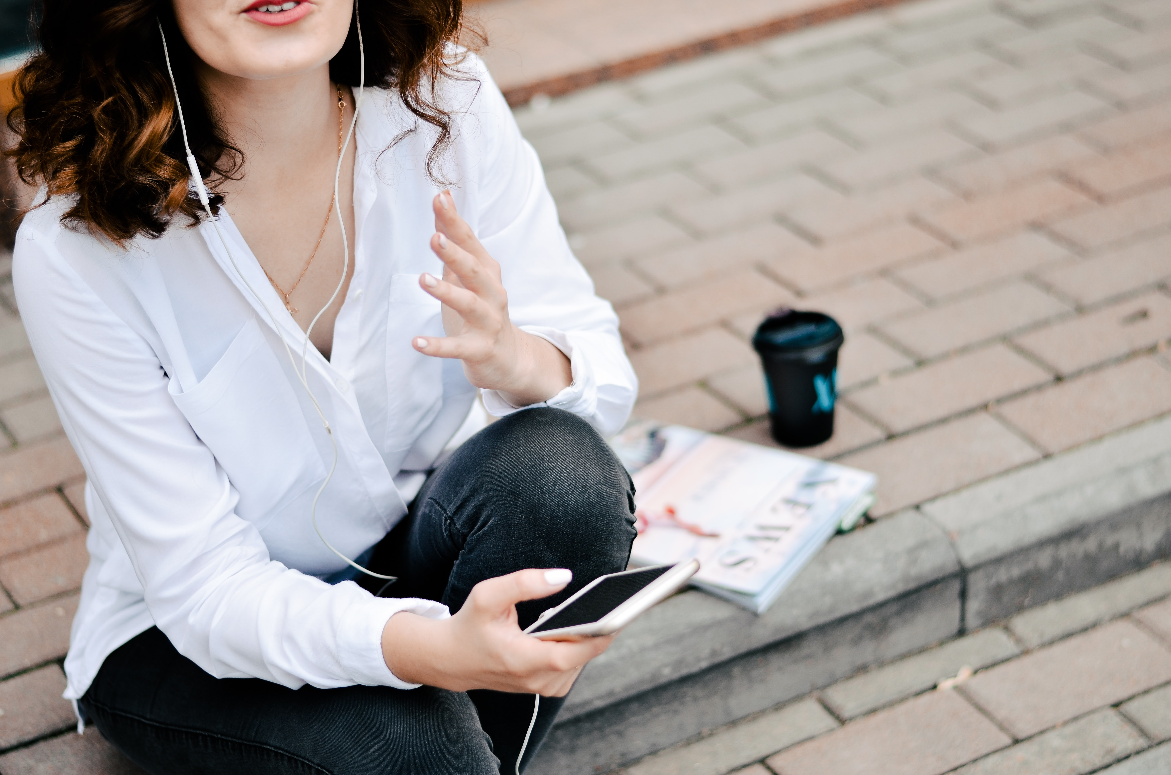 woman holding smartphone while sitting on brick pavement during daytime
