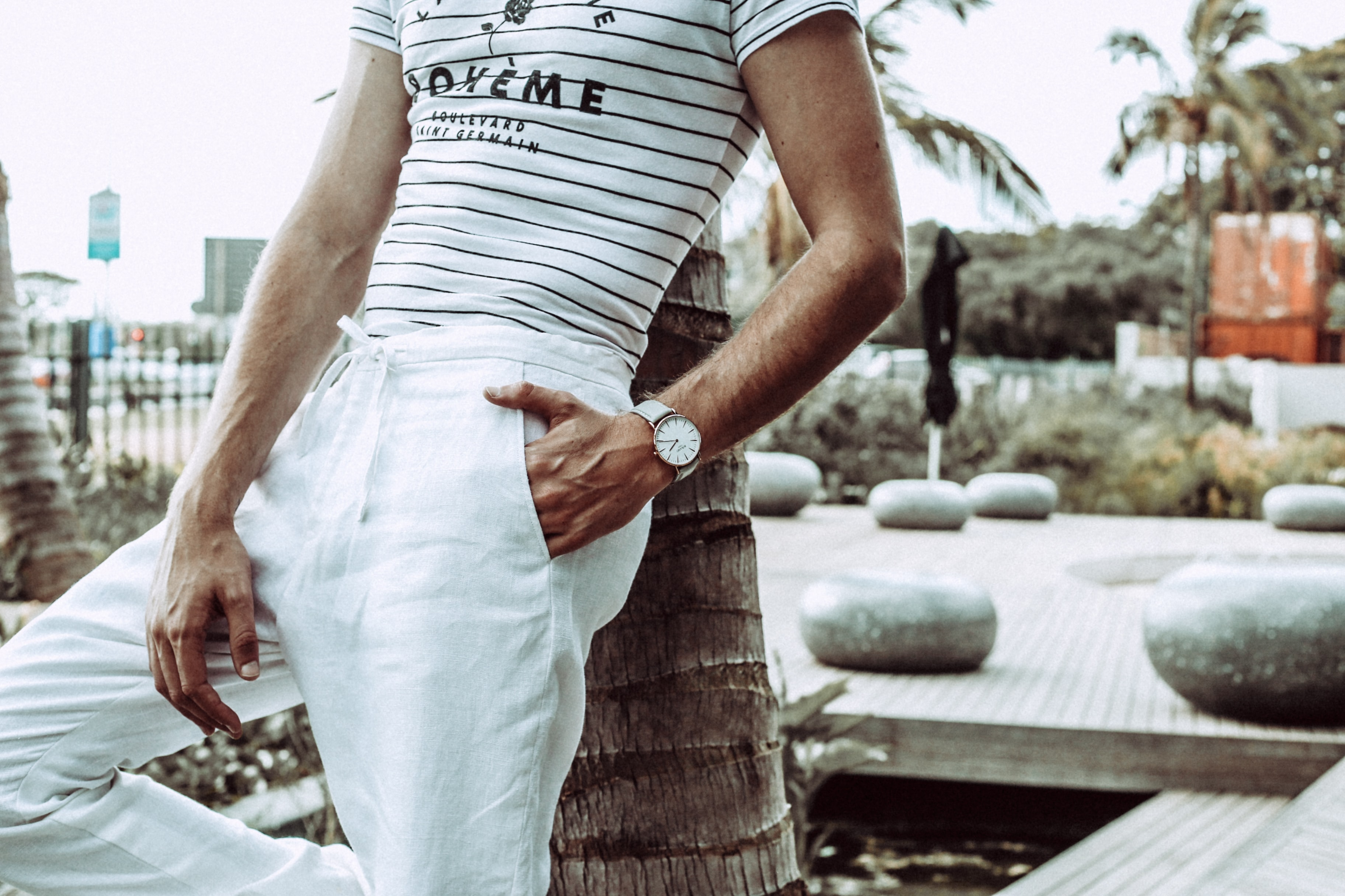 person in white pants wearing white analog watch