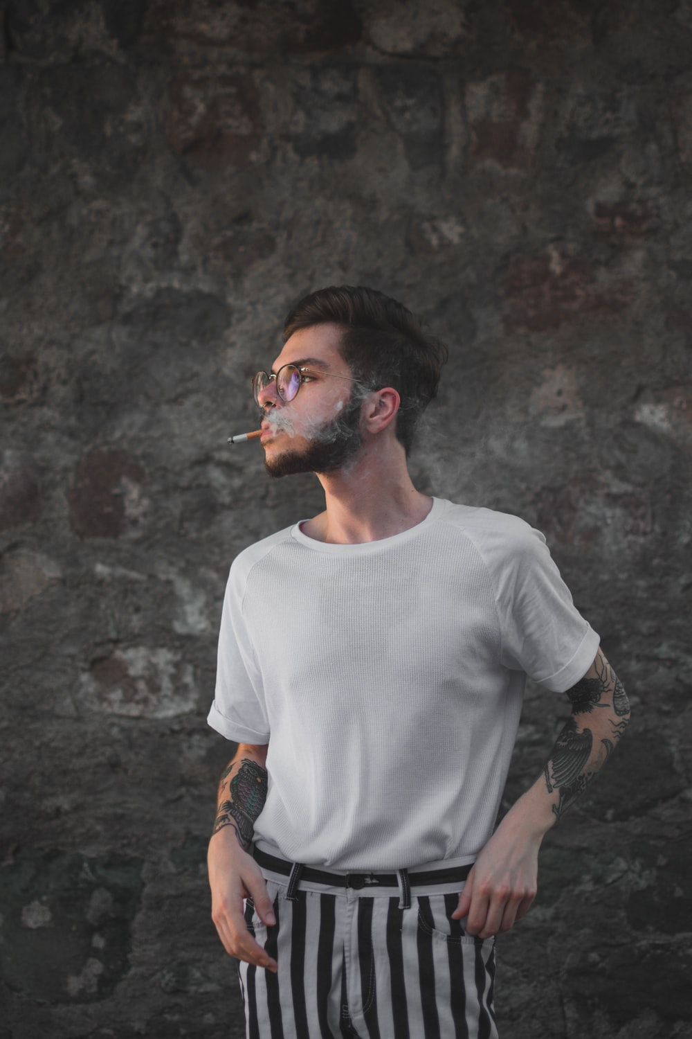 man in white crew-neck t-shirt and striped pants smoking by wall