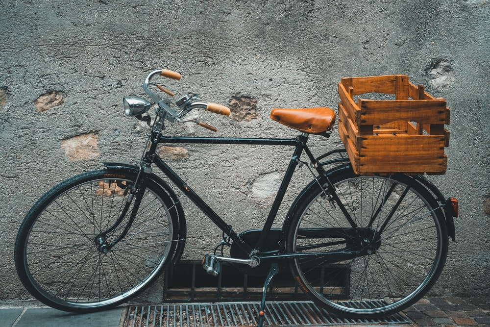 black commuter bike parked beside gray wall