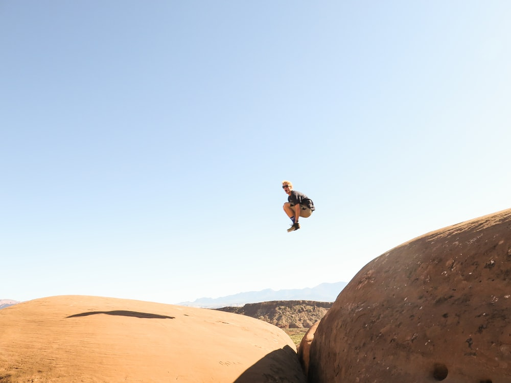 man jumping on rock formation at daytime