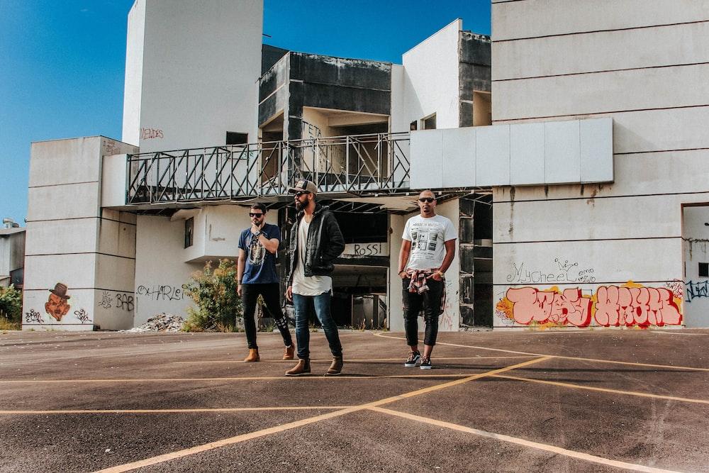 three men standing near building