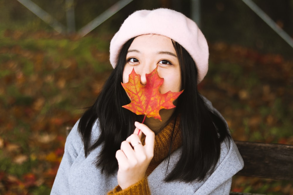 woman holding maple leaf and wearing pink hat