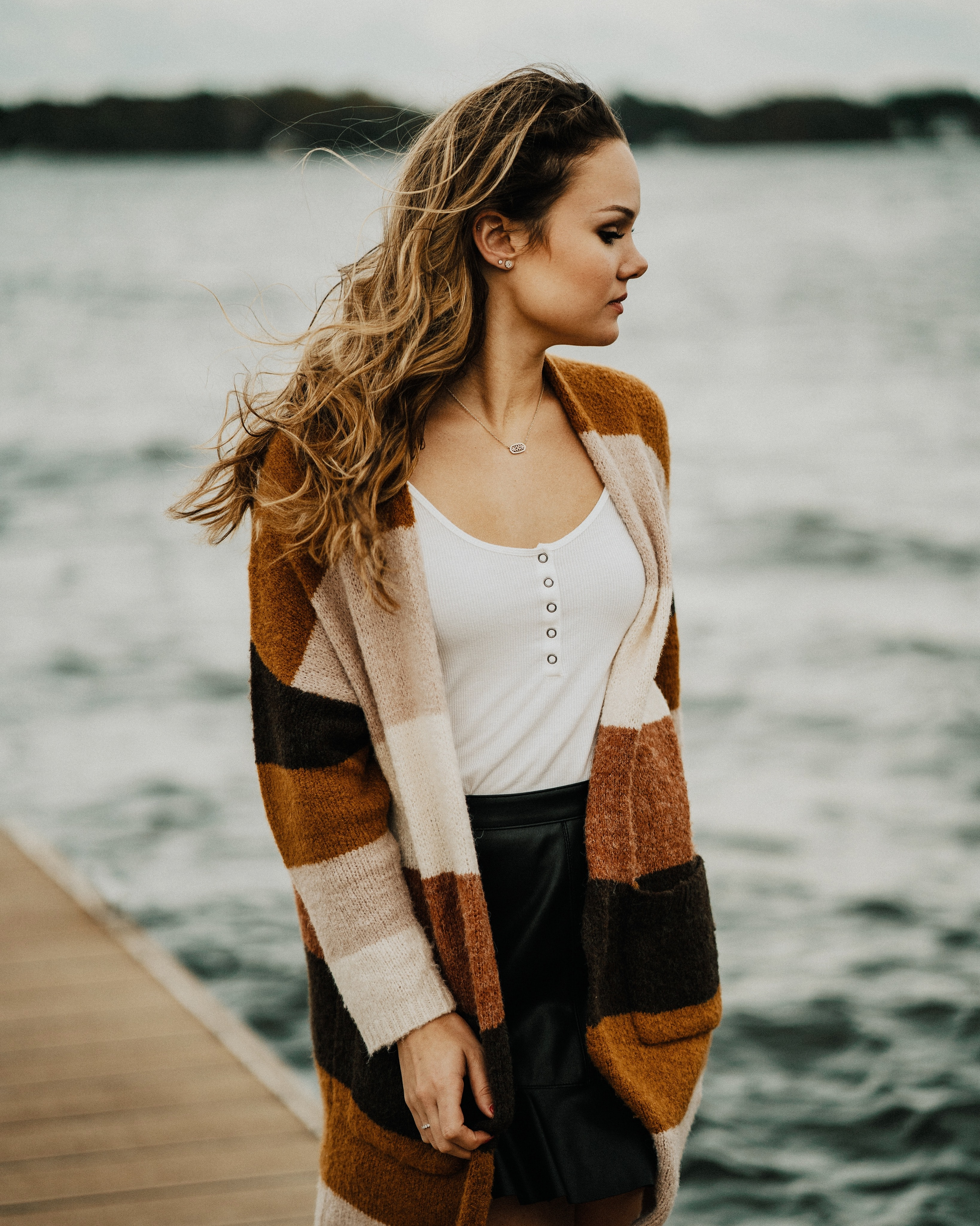 woman wearing brown, black, and white coat on dock