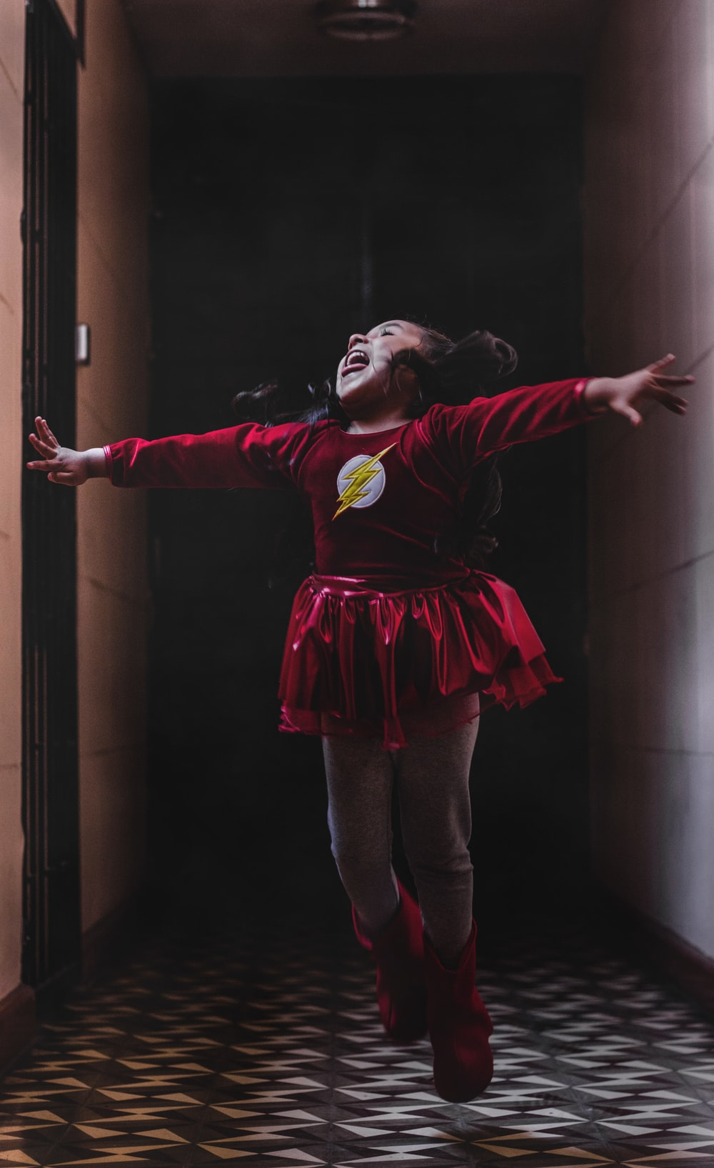 laughing and jumping girl in DC Flash costume in room