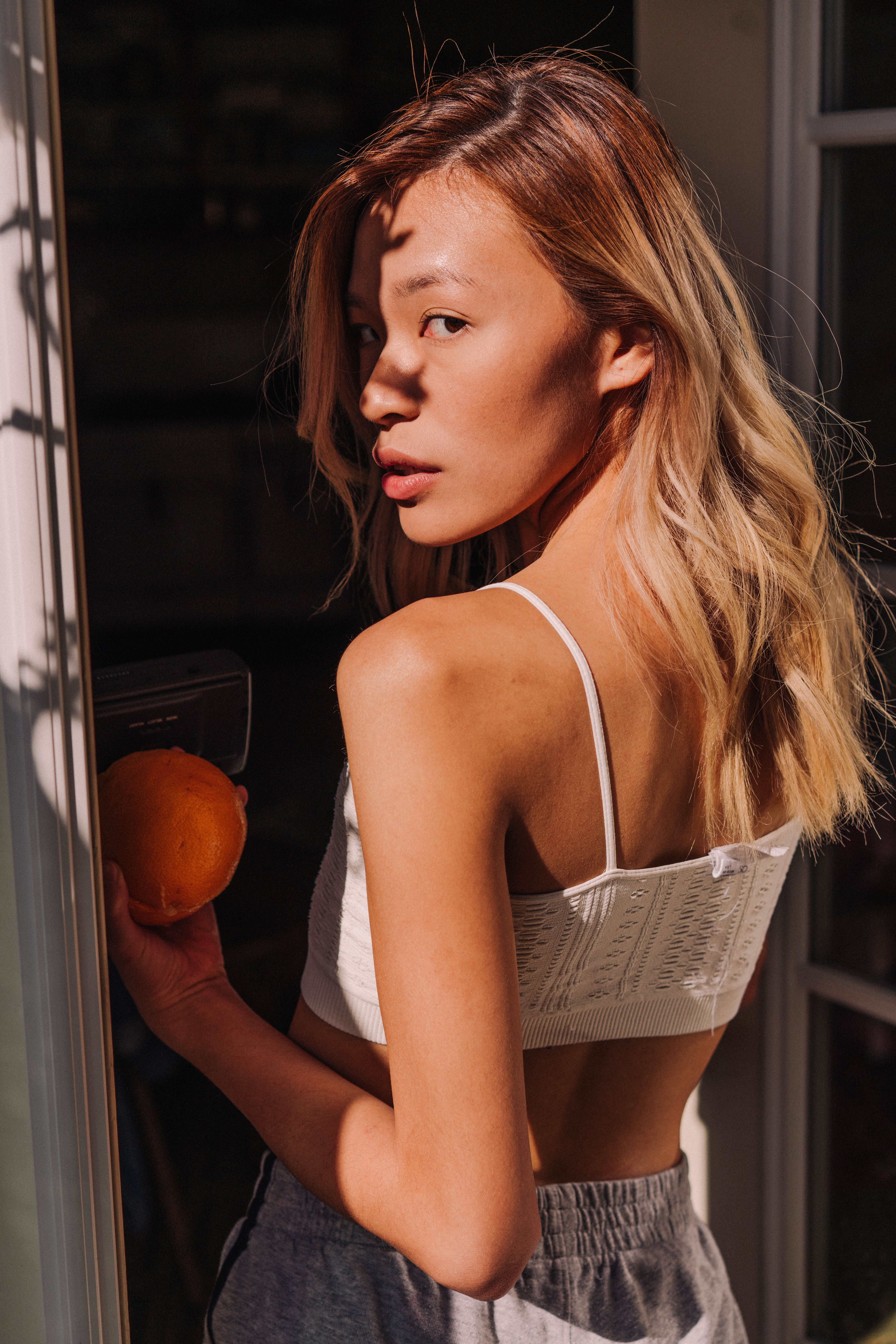 woman wearing white spaghetti strap crop top and holding orange fruit