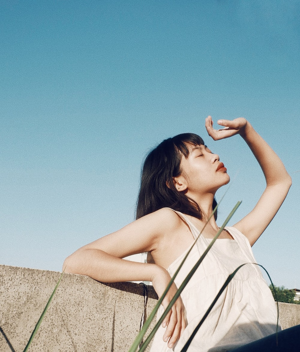 woman leaning on wall covering her face