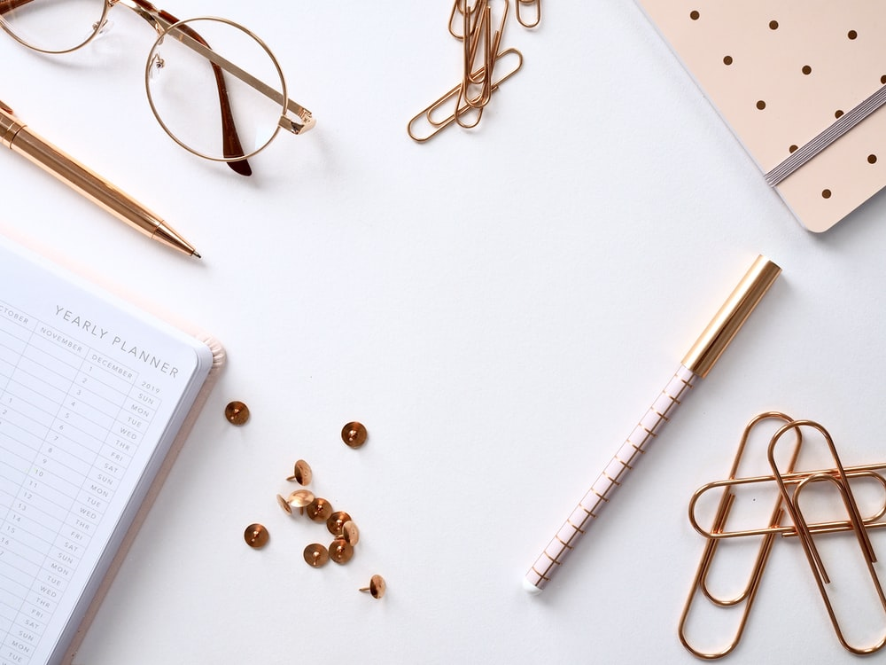 book beside thumbtacks, pens, paperclips, and eyeglasses