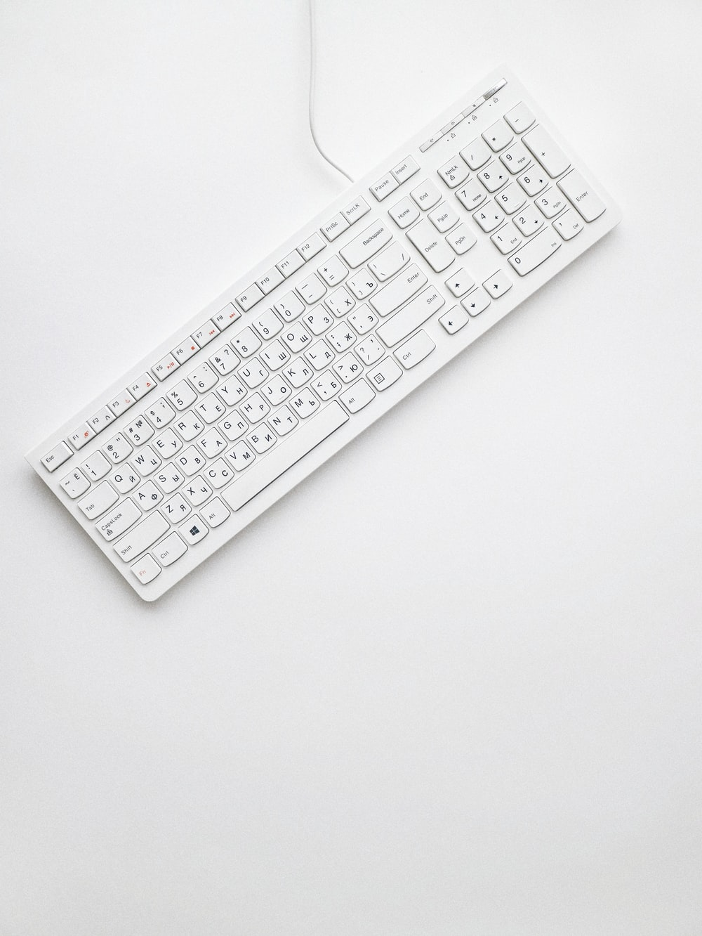 white corded computer keyboard on white surface