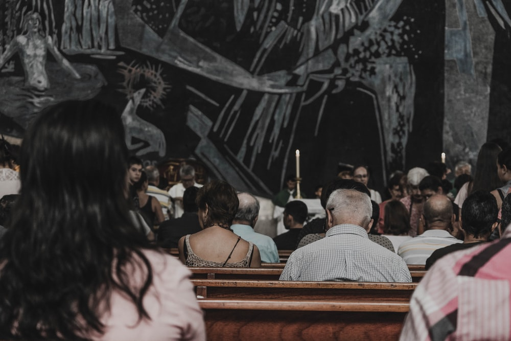 people sitting on pew bench in church