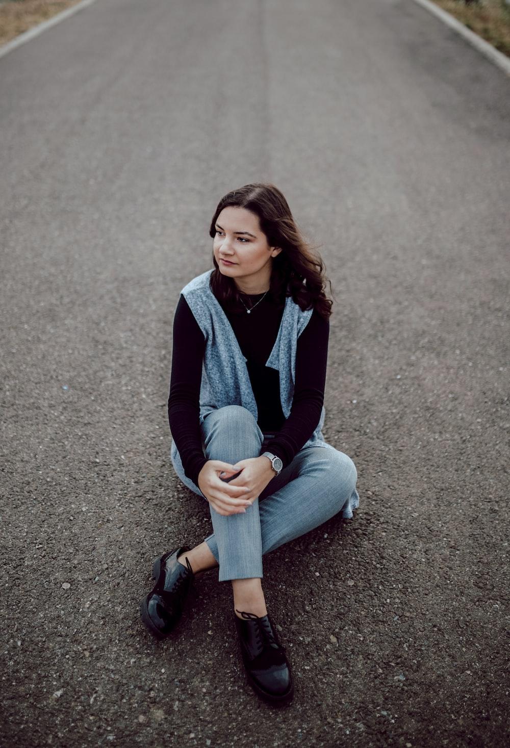woman sitting on concrete road
