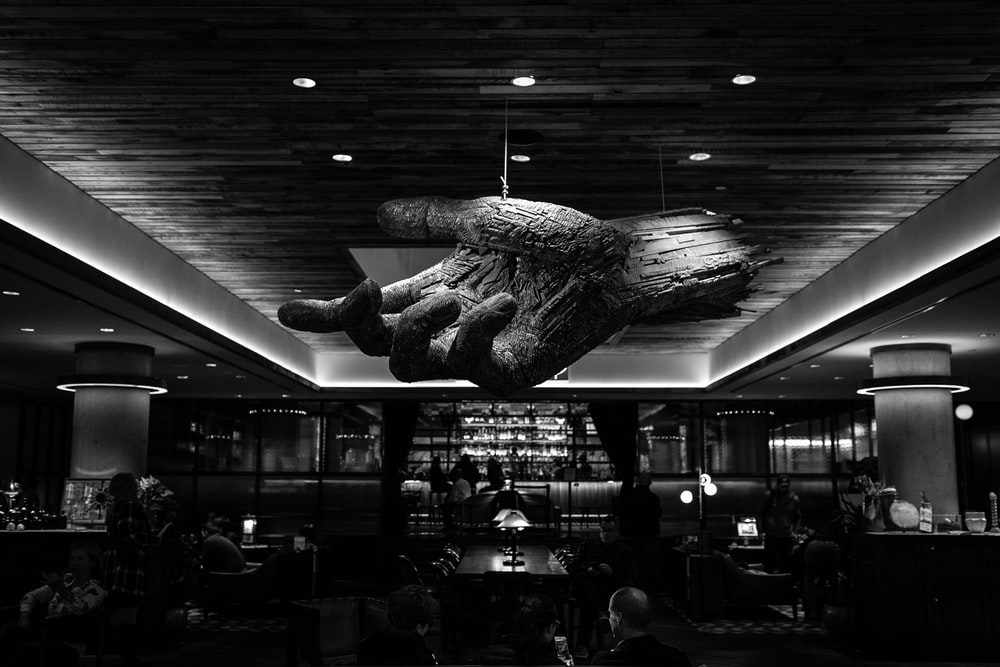 grayscale photography of restaurant with 3D hand ceiling