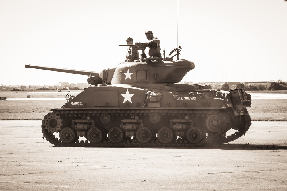 two people riding on battle tank