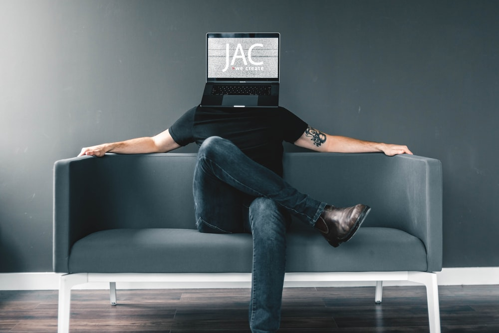 man in black shirt and blue jeans sitting on gray sofa with JAC mask