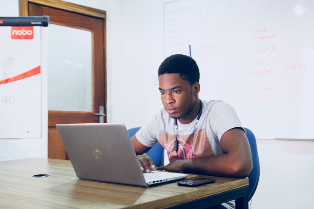 man in grey shirt using grey laptop computer