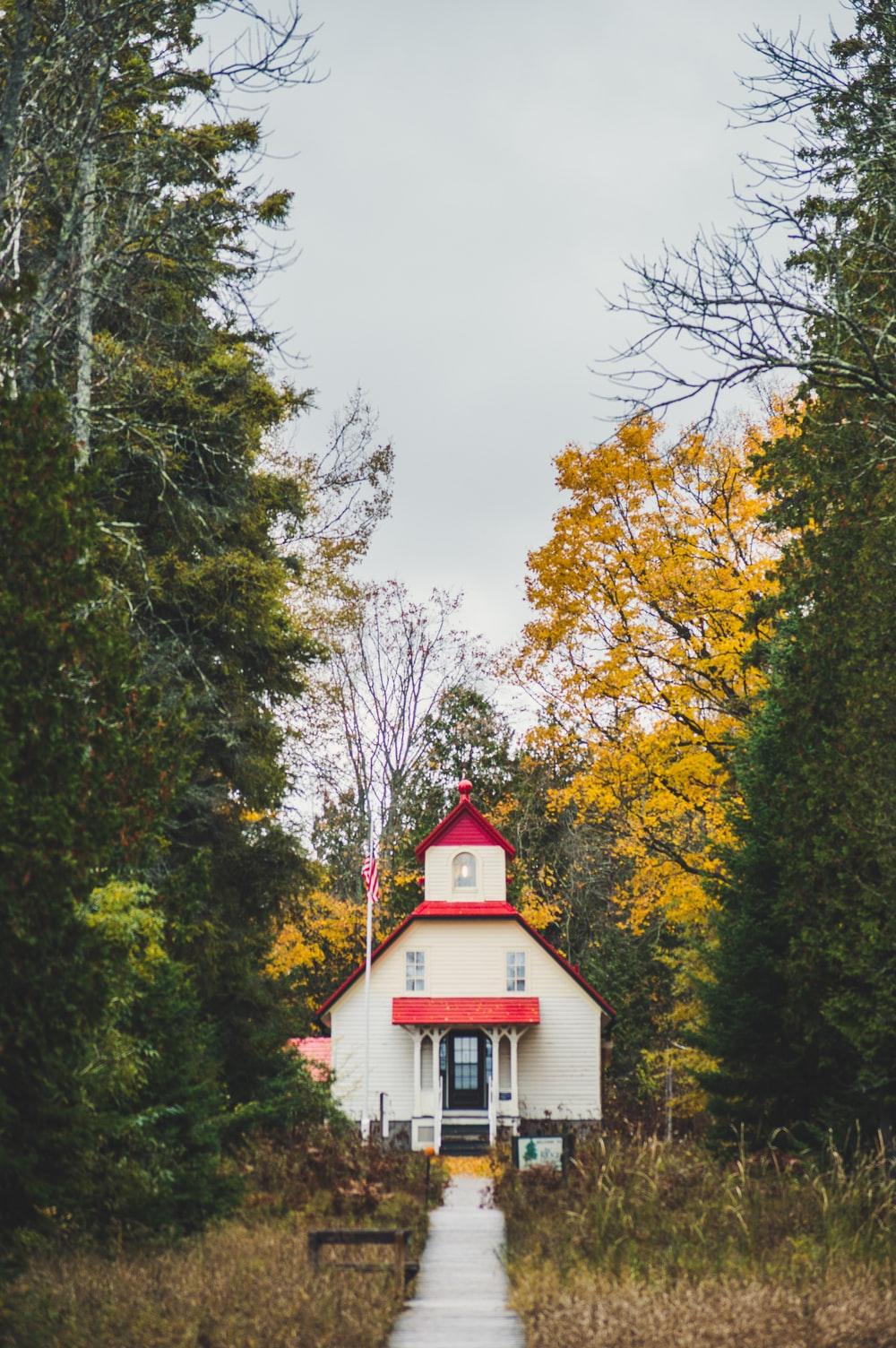 white and red house surrounded by trees