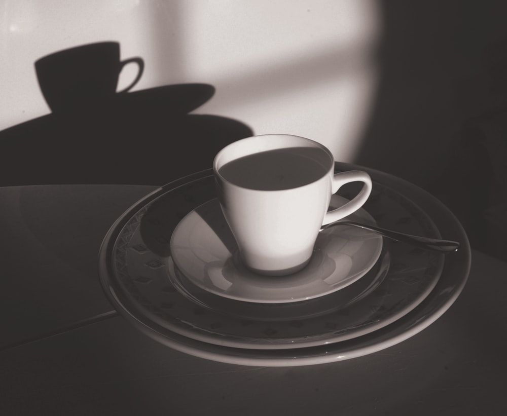 grayscale photography of mug with spoon on top of saucer and plate