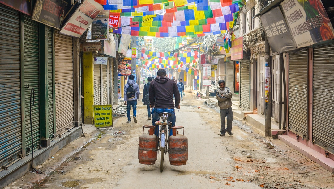 Interesting early morning scene in the Thamel business  area in Kathmandu (Nepal). The roads are a bit dusty and the sight of a cyclist carrying two gas canisters caught my attention.