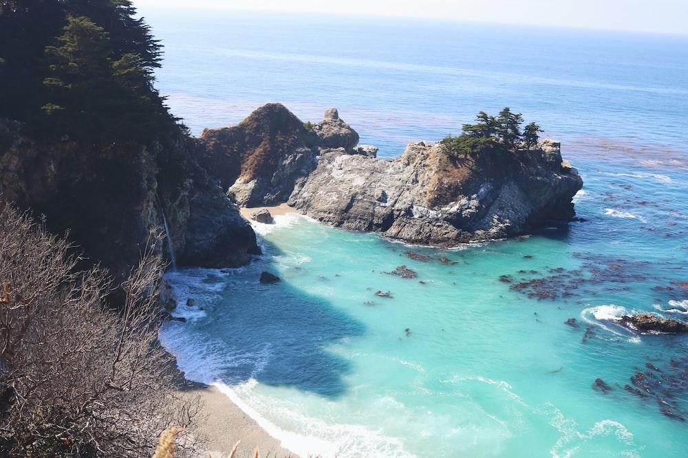 calm body of water near cliff