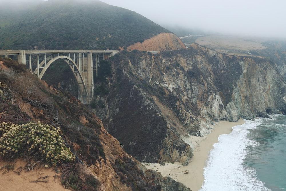 gray and brown bridge beside beach during daytime