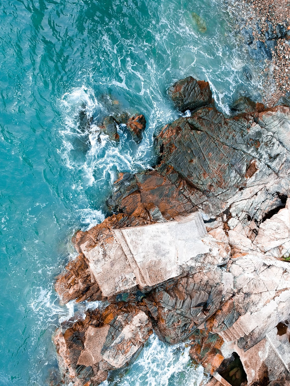 high-angle photography of body of water near rock formation