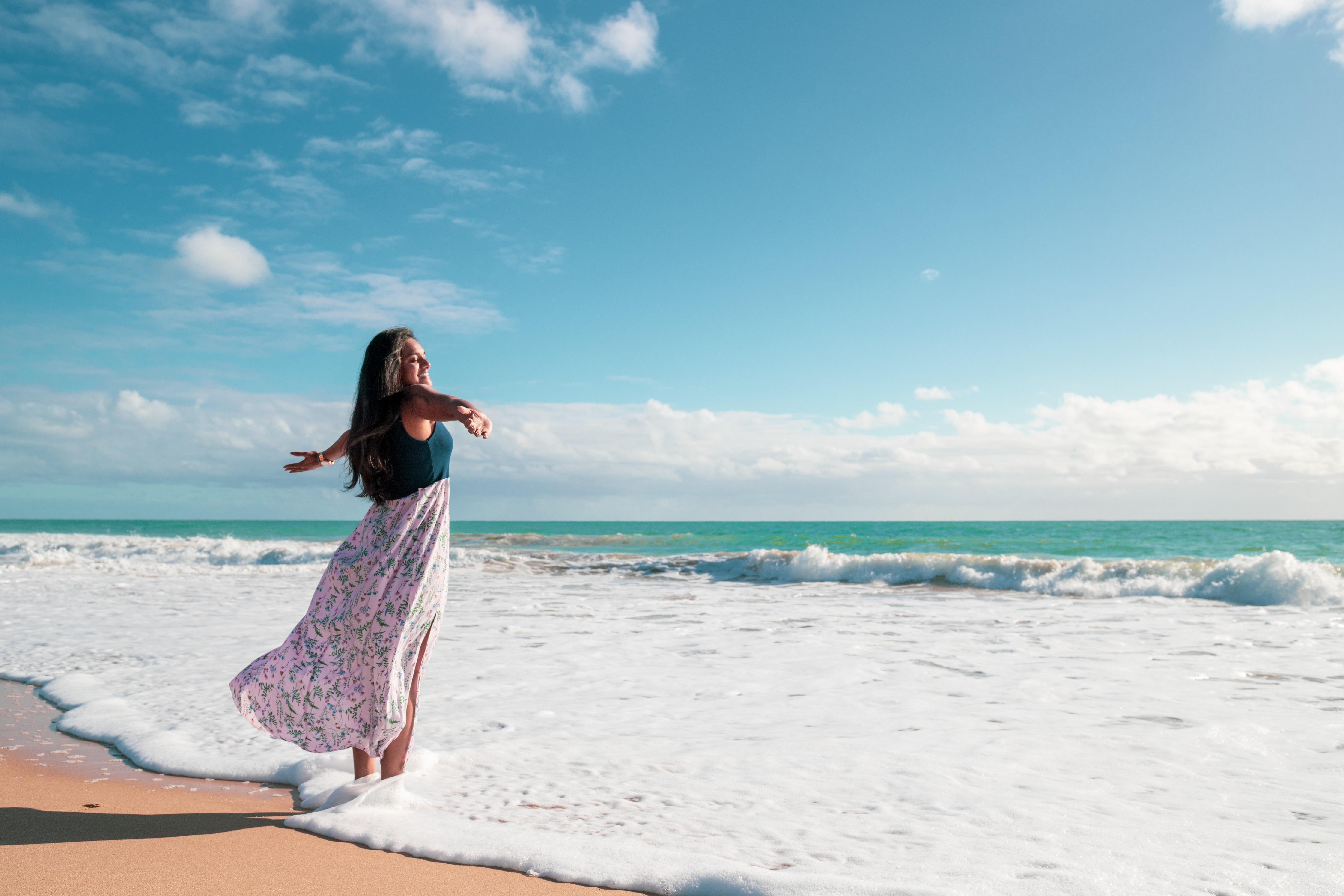 woman spreading her arms while standing near shore with ocean in background during daytime