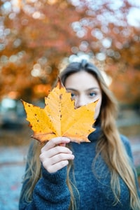 focus photography of woman holding yellow leaf during daytime