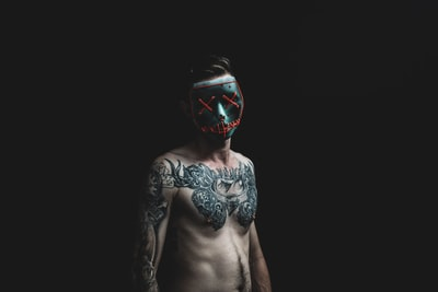 man standing while wearing black mask tattoo zoom background
