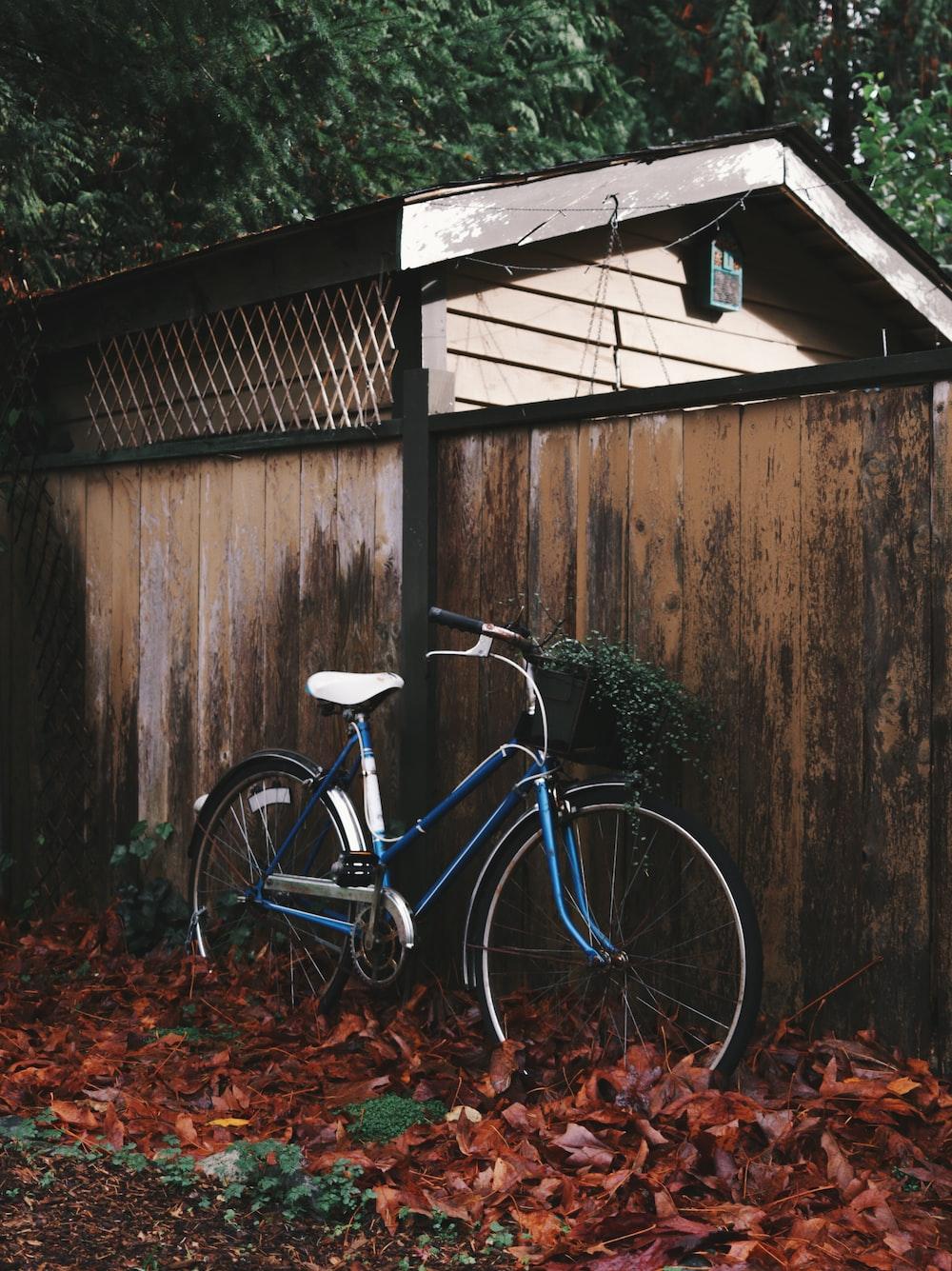 blue beach cruiser bike parked beside wall