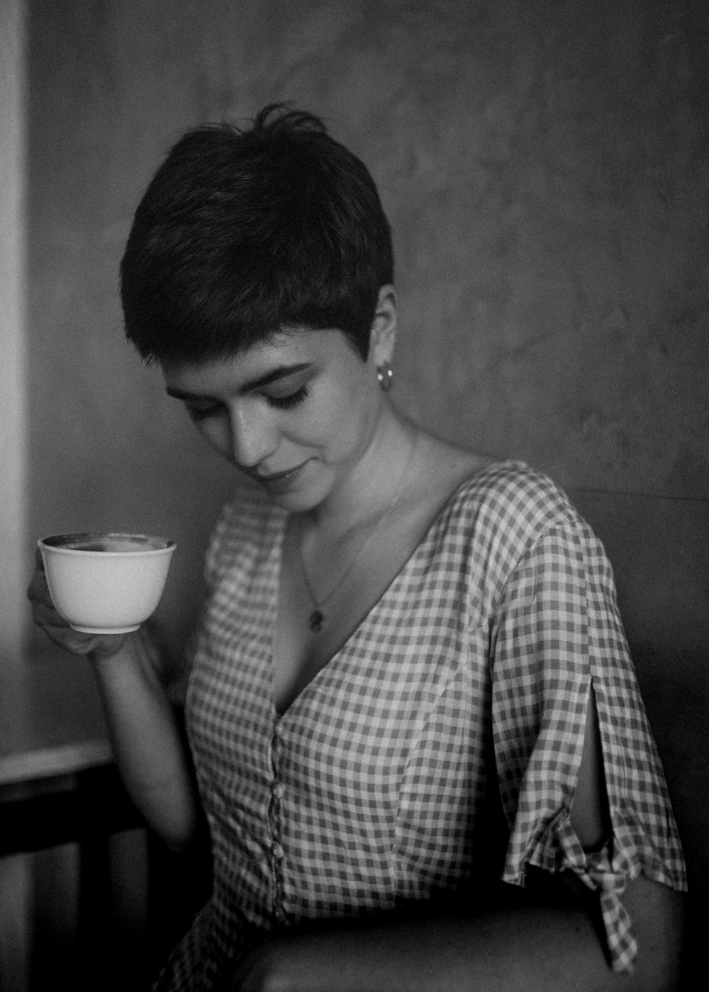 grayscale photography of woman holding cup