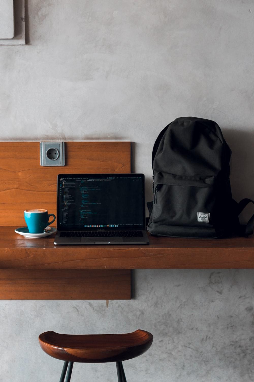 laptop computer beside backpack and coffee mug