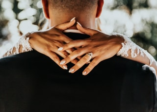 bride with hands on back of man wearing black formal top