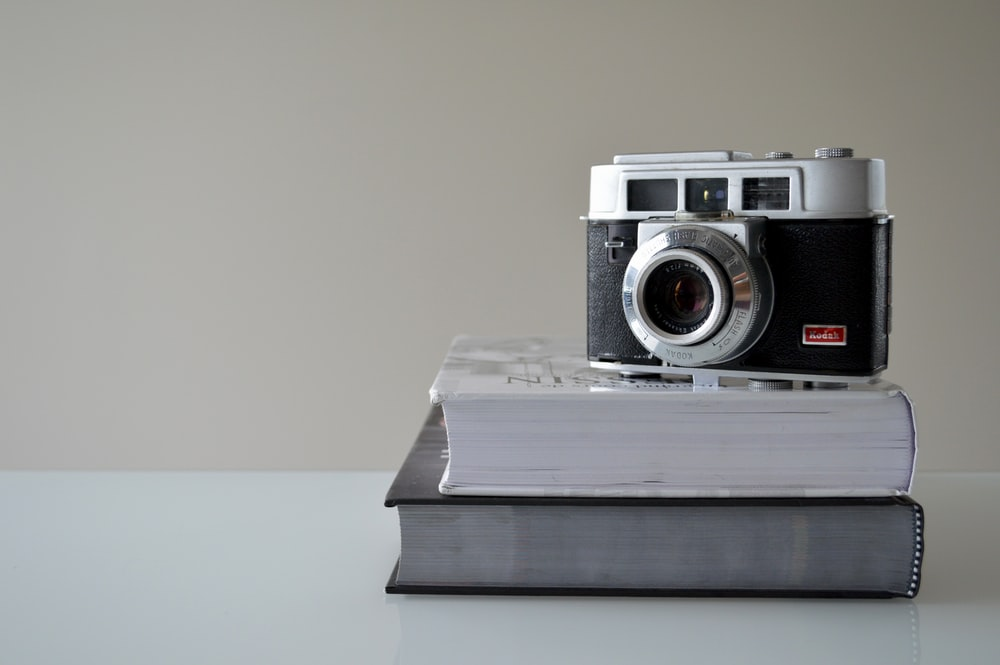 black point-and-shoot camera on book