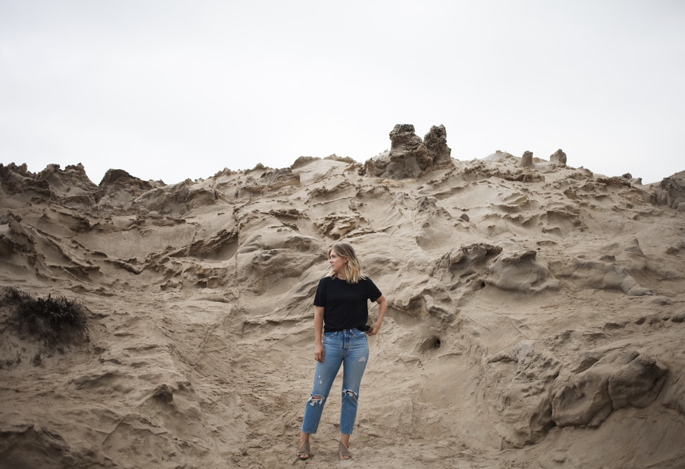 woman in black T-shirt standing on beige mountain