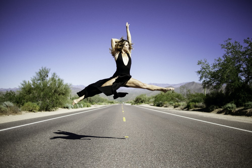 time-lapse photography of woman doing split in air in the middle of road