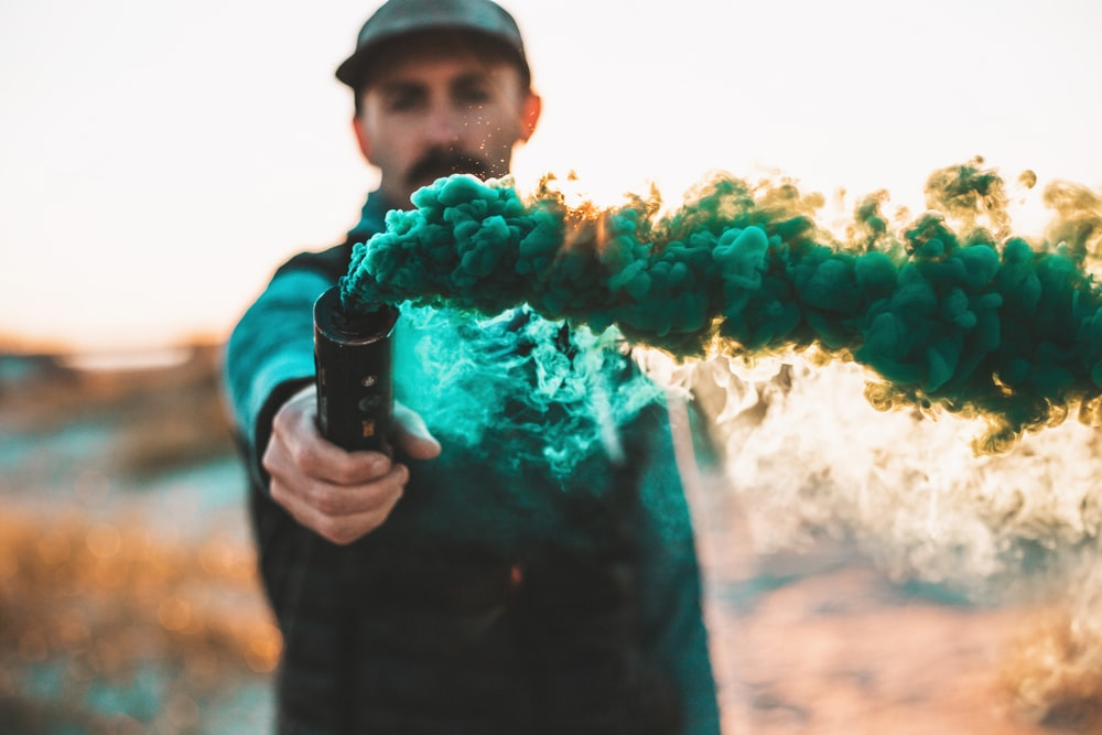 man holding bottle with green smoke