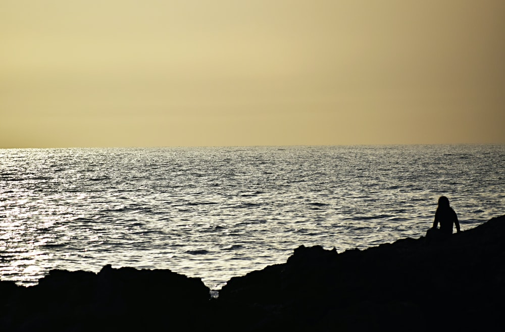 silhouette of person sitting in front ocean