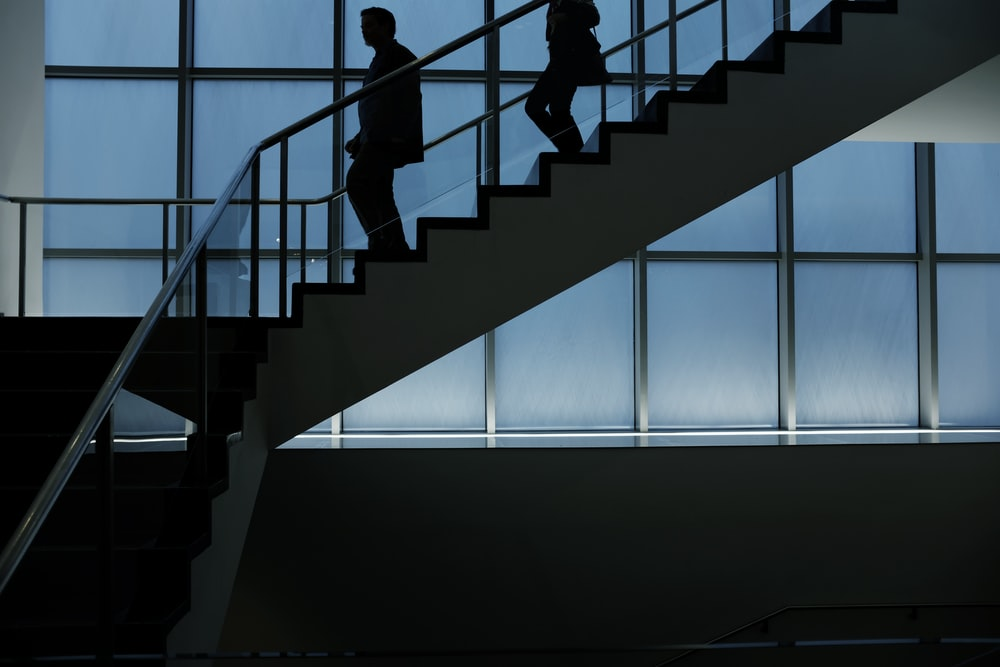 two person walking down on stairs