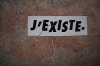 white board with J'existe. text