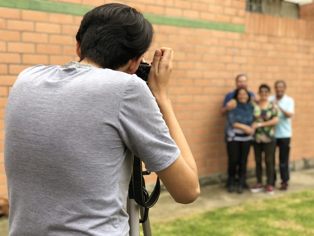 man taking picture to four people standing beside wall