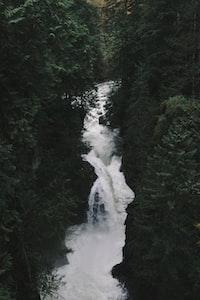 waterfalls in between green grass during daytime