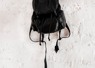 black leather backpack on wall