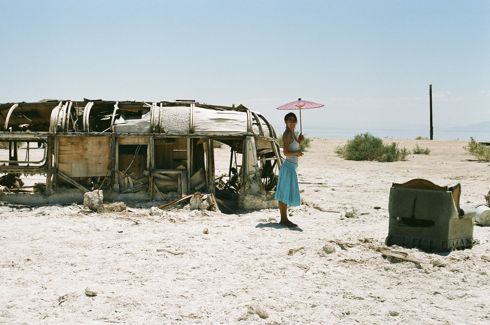 woman standing beside abandoned bus