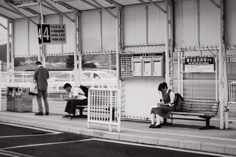 students sitting on bench near bus stop