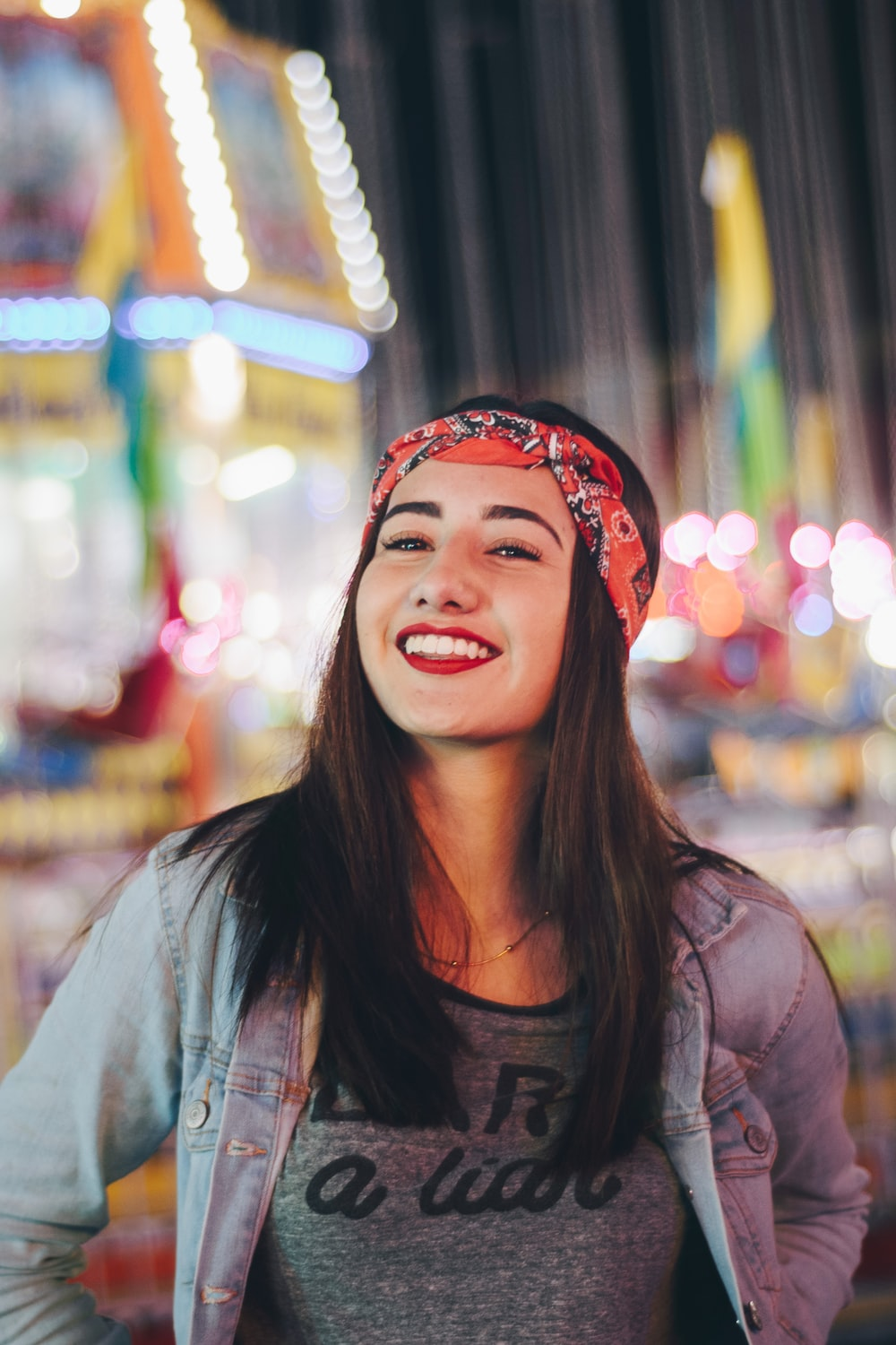 selective focus photography of smiling woman wearing red and black bandana