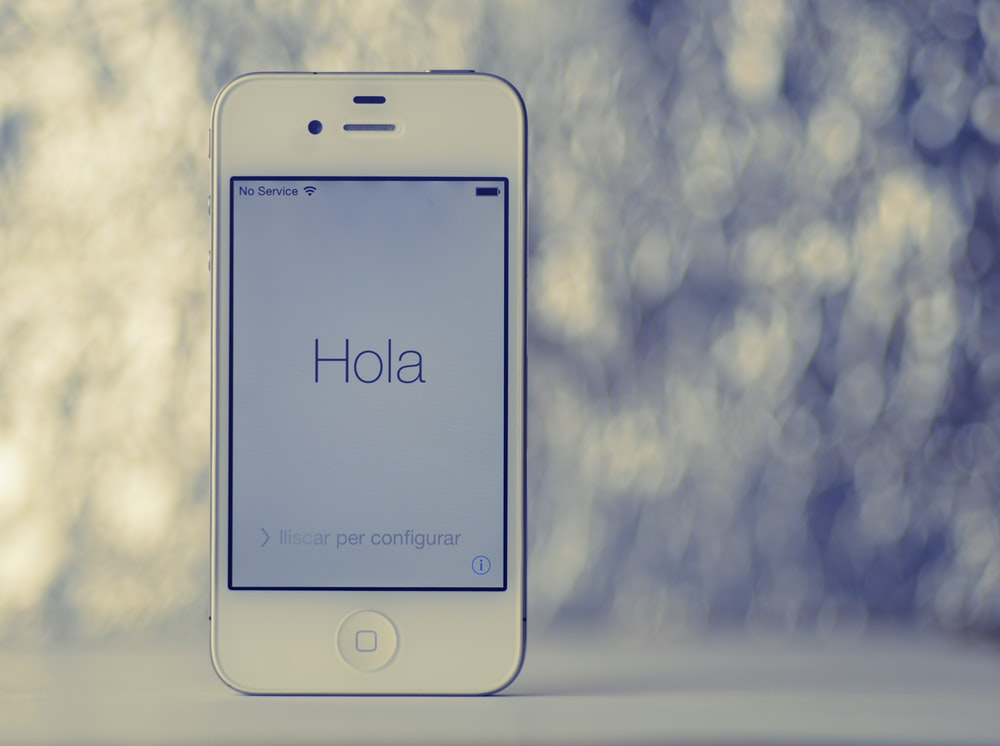 turned-on white iPhone 4 with Hola text greeting display