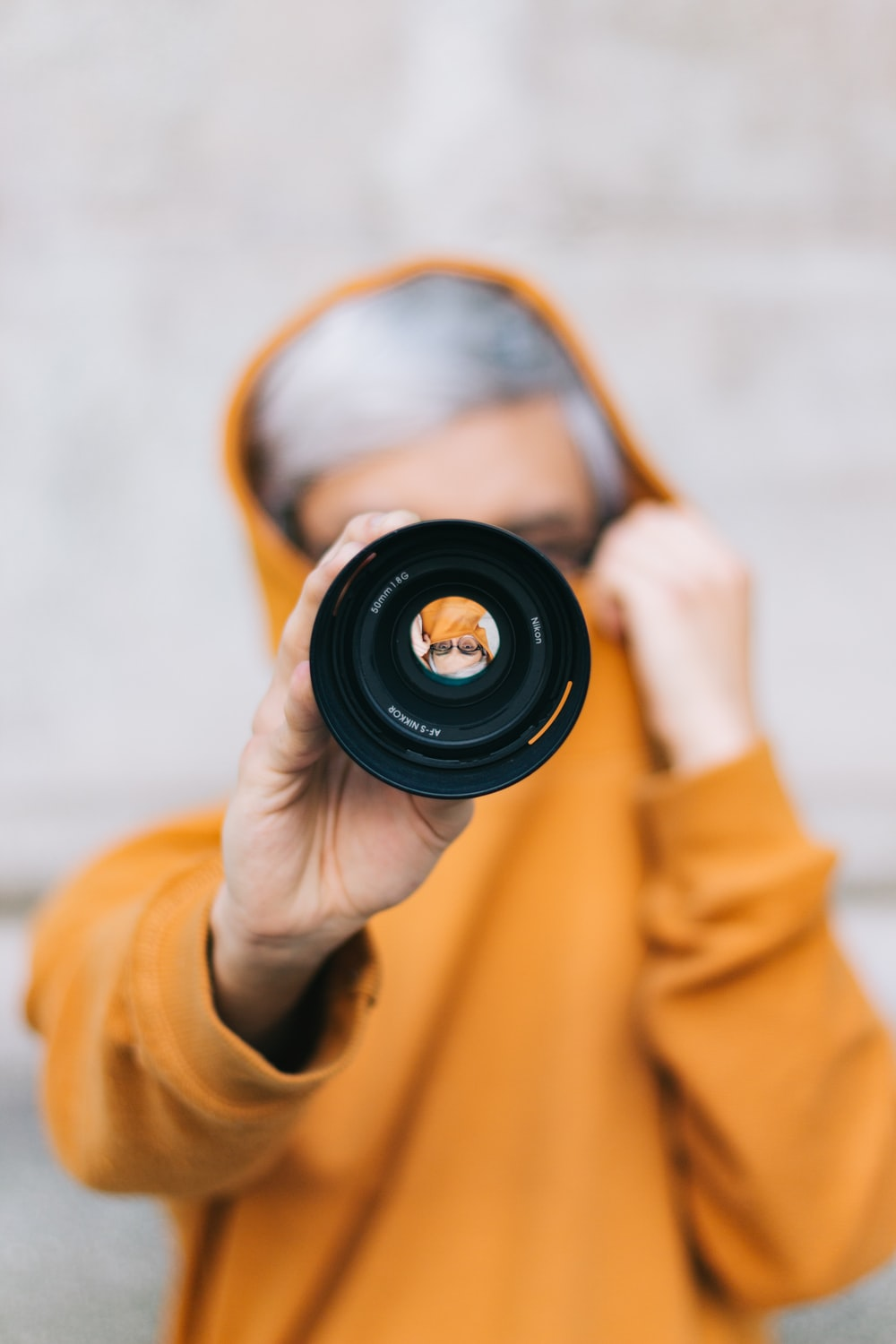 view of person in yellow hoodie holding camera lens