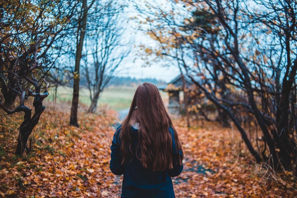 woman walking on dirt road beside bare trees