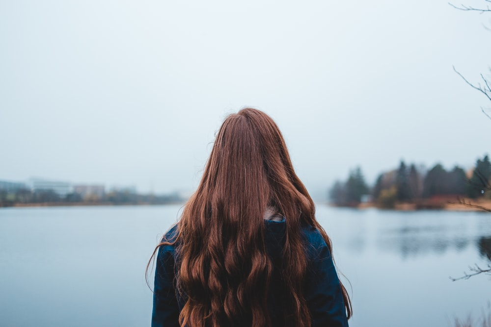 woman looking at blue body of water