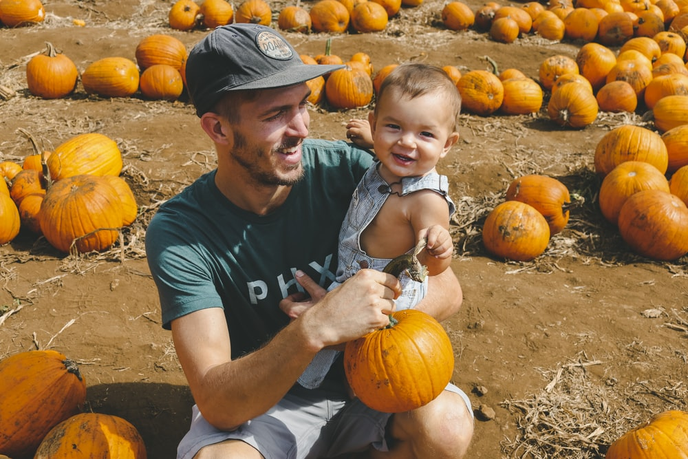 smiling man carrying toddler boy while holding pumpkins